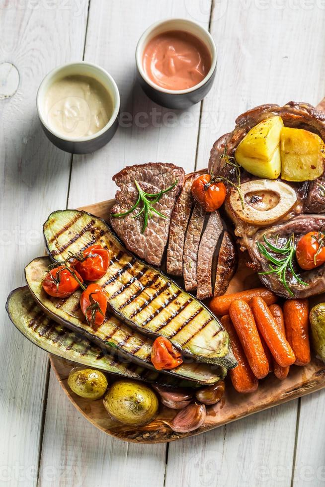 Roasted steak and vegetables with herbs on wooden board photo