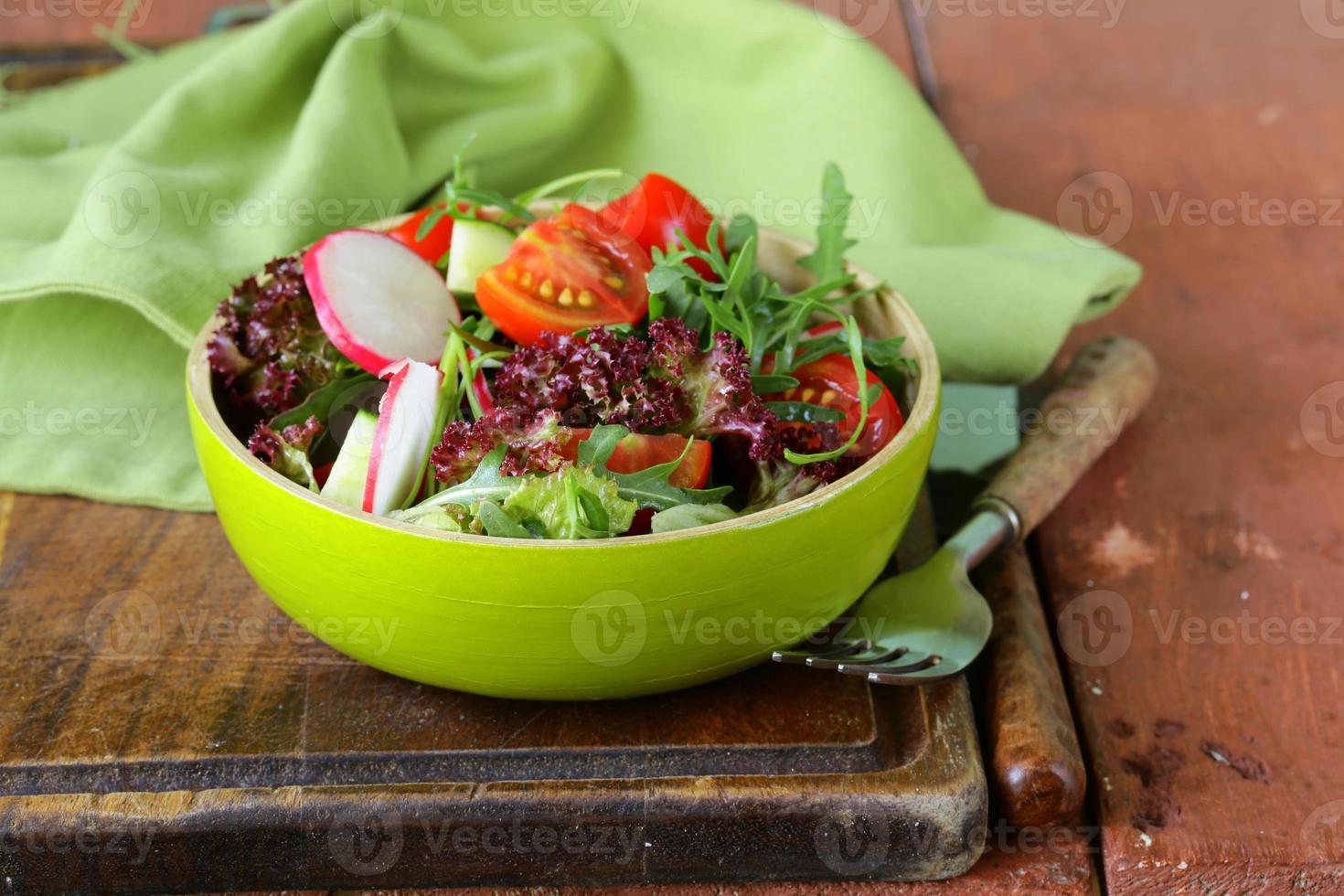 fresh salad with arugula, radish and tomatoes photo