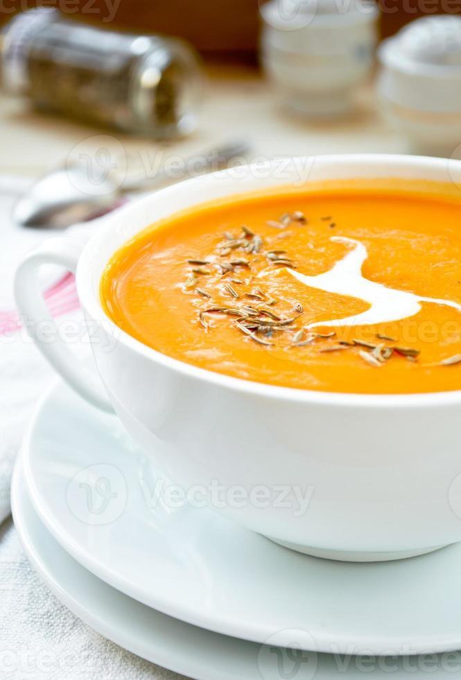 Vegetarian carrot-pumpkin cream soup with garlic and cumin photo