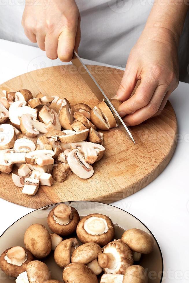 cortar los champiñones castaños en rodajas finas foto