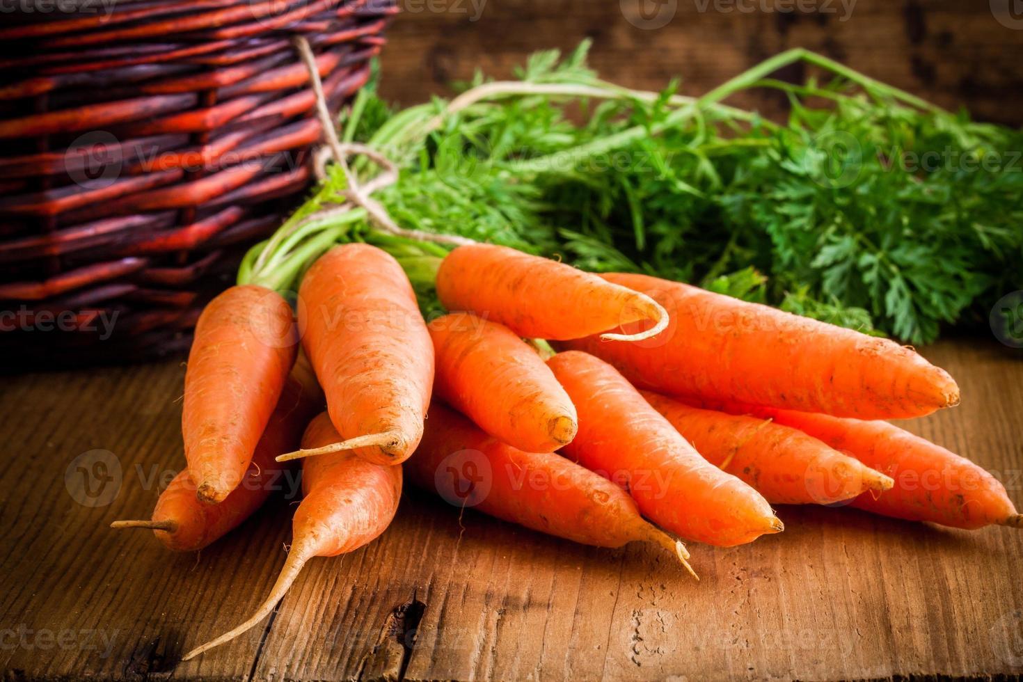 Fresh Organic Carrots on wooden background photo