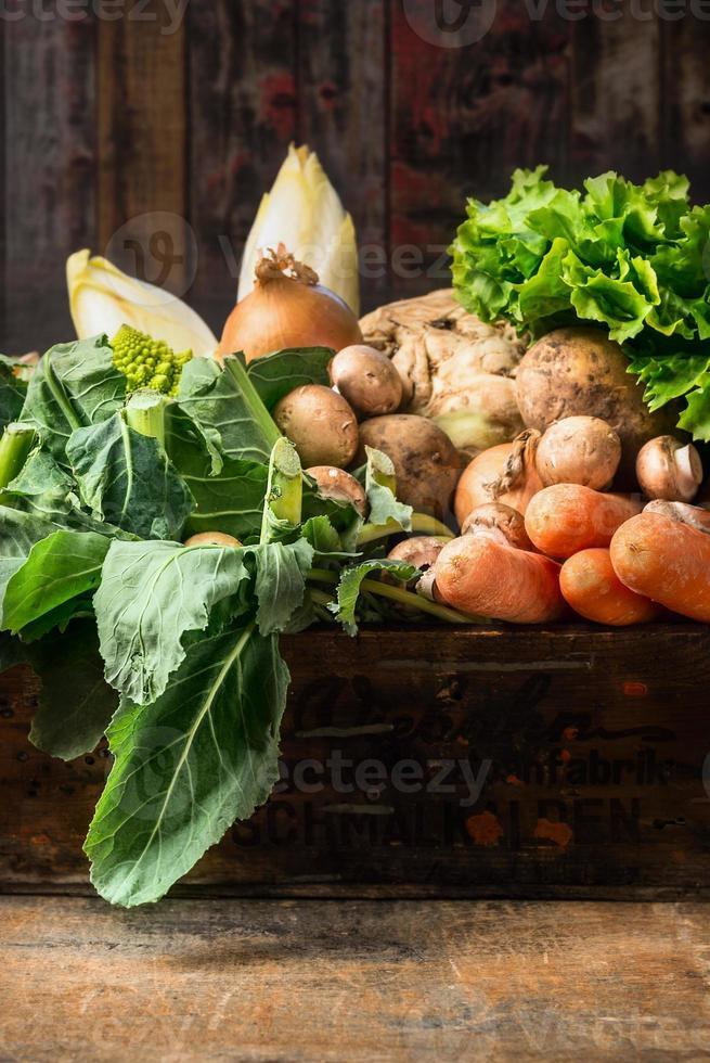 Caja de verduras orgánicas sobre fondo de madera vieja foto