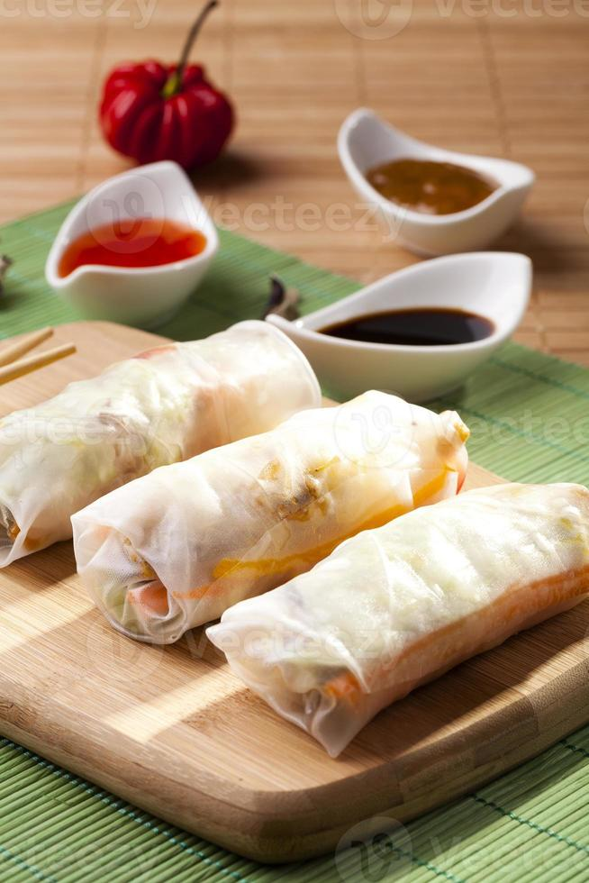 Portion of spring rolls on a bamboo board photo