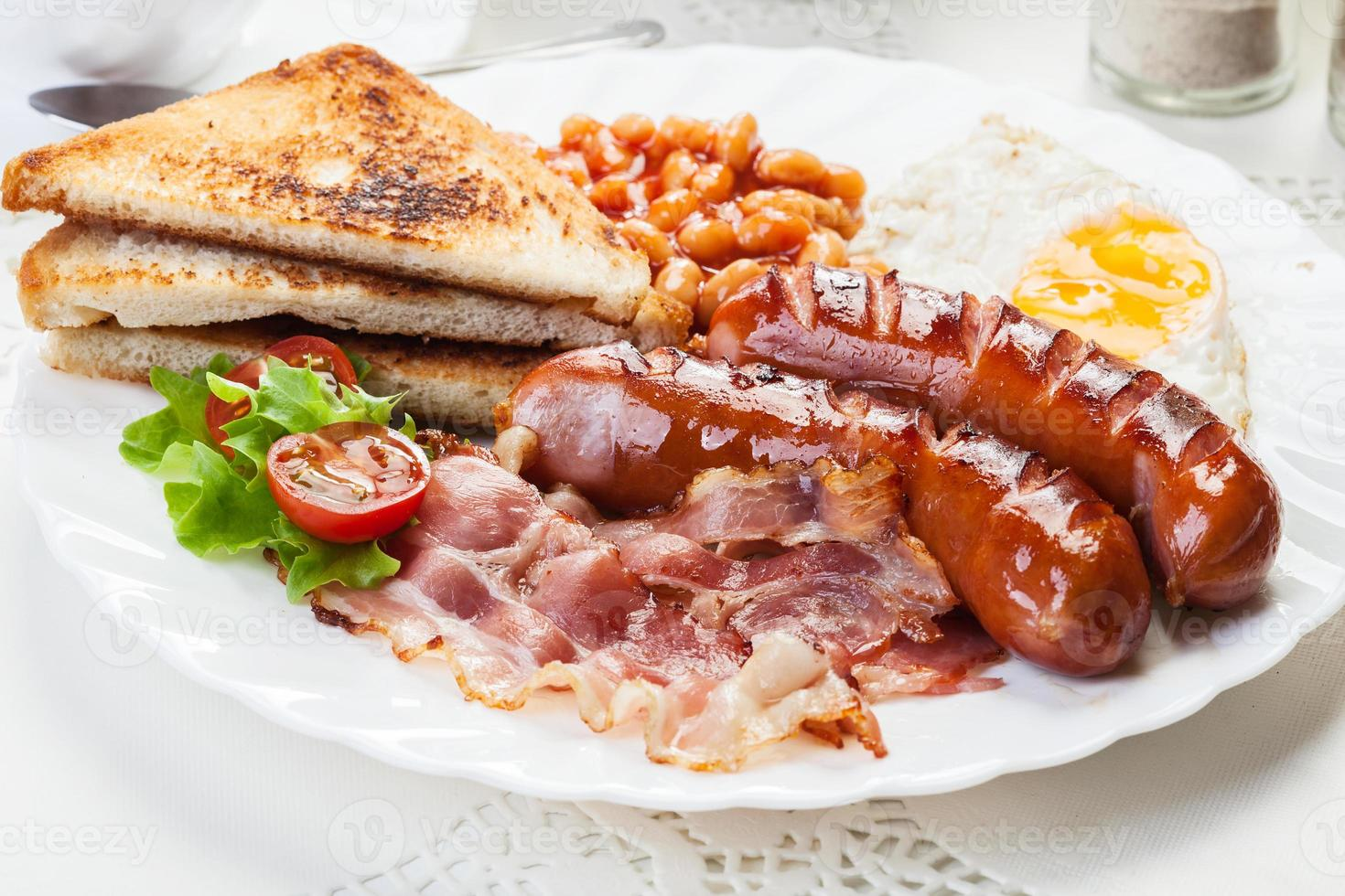 Full English breakfast with bacon, sausage, egg and baked beans photo