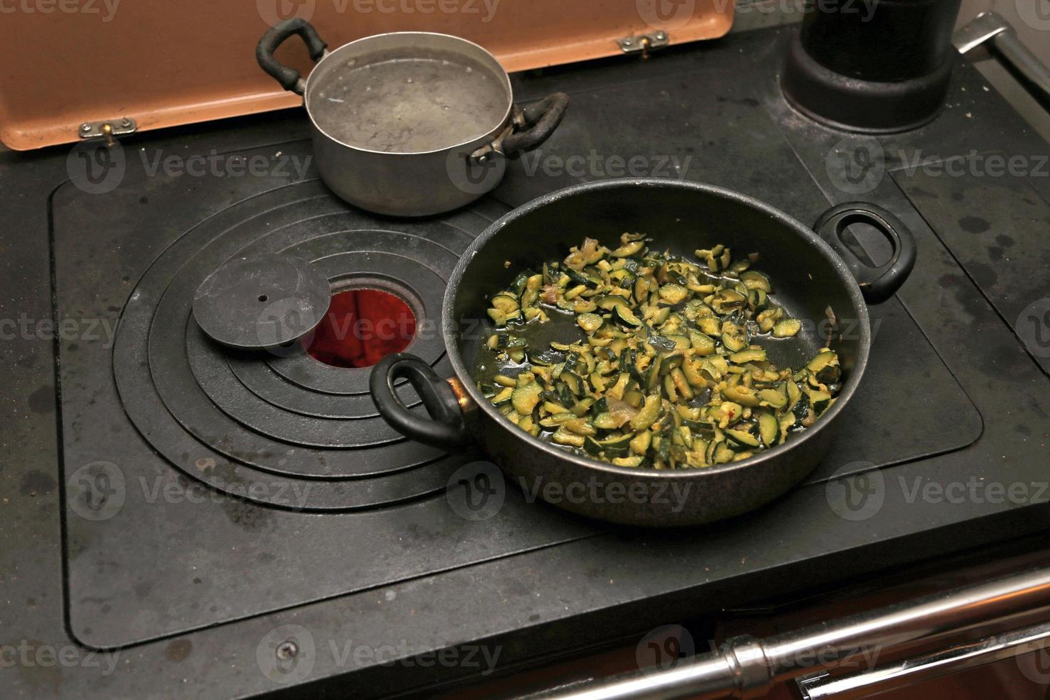 green Zucchini with pot over the stove in the mountains photo