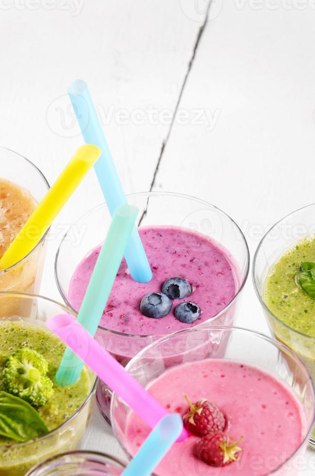Batidos variados de frutas y verduras en la mesa blanca foto
