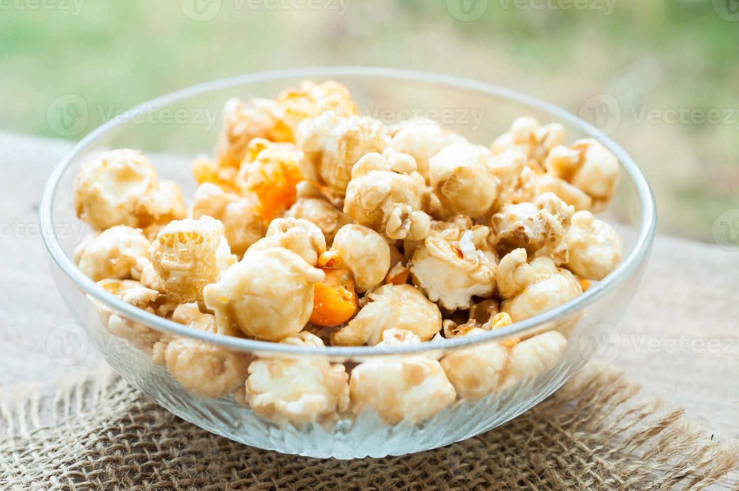 bowl of popcorn on a wooden table, caramel popcorn photo