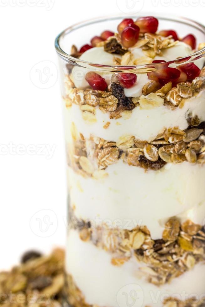Glass of Muesli with fruits and yogurt isolated on white photo