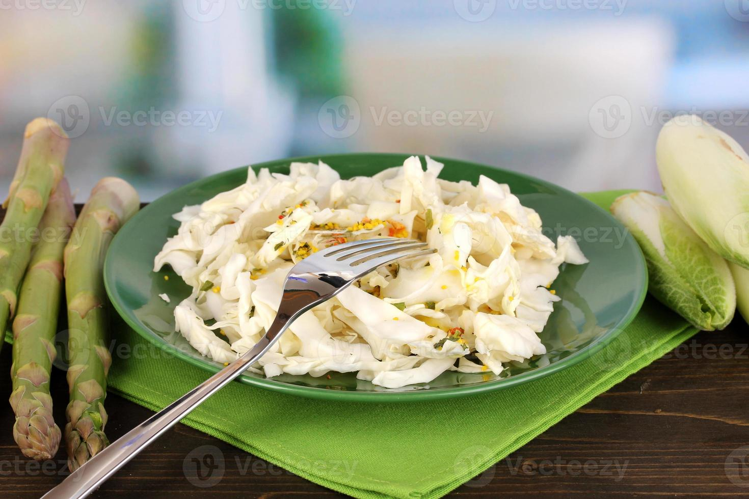 Plate with coleslaw, asparagus and chicory on table photo