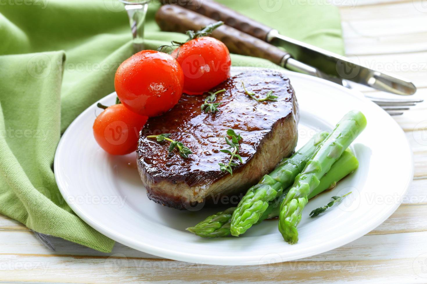 grilled meat beef steak with vegetable garnish (asparagus and tomatoes) photo