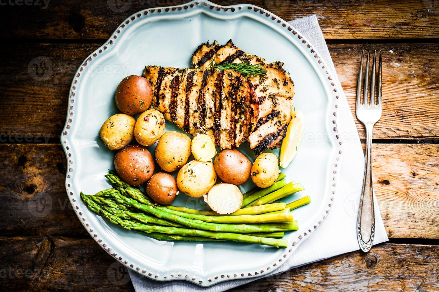 Grilled chicken with potatoes and asparagus on wooden background photo