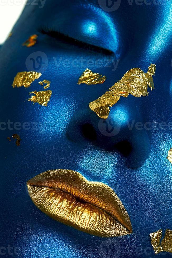 modelo femenino con piel azul y labios dorados. maquillaje de halloween foto