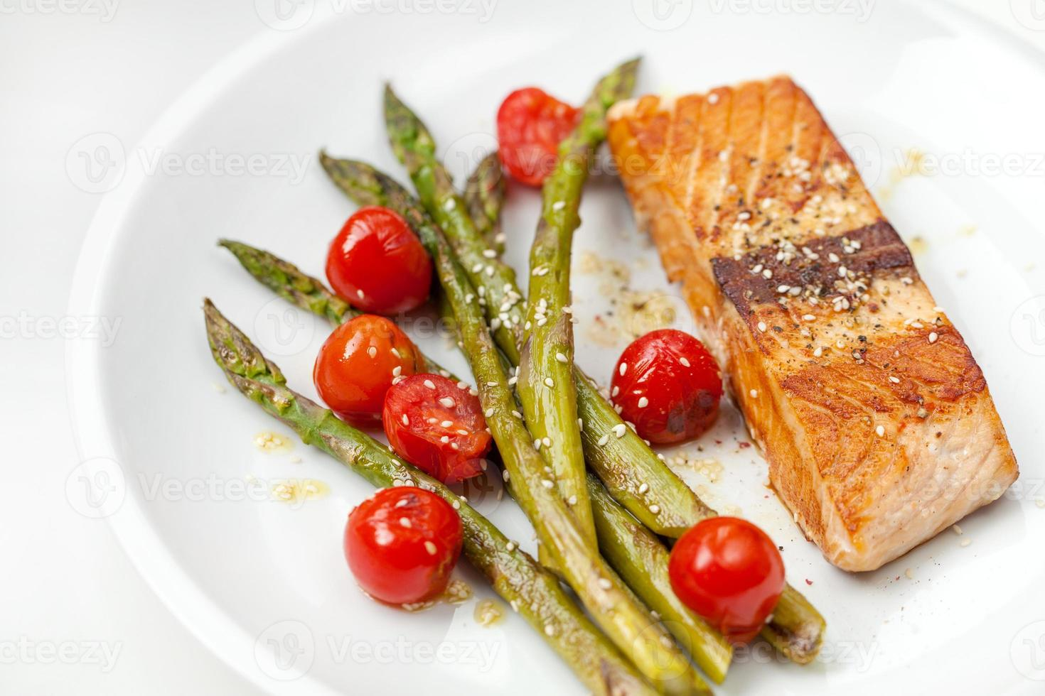 Salmon fillet with asparagus and cherry tomatoes photo