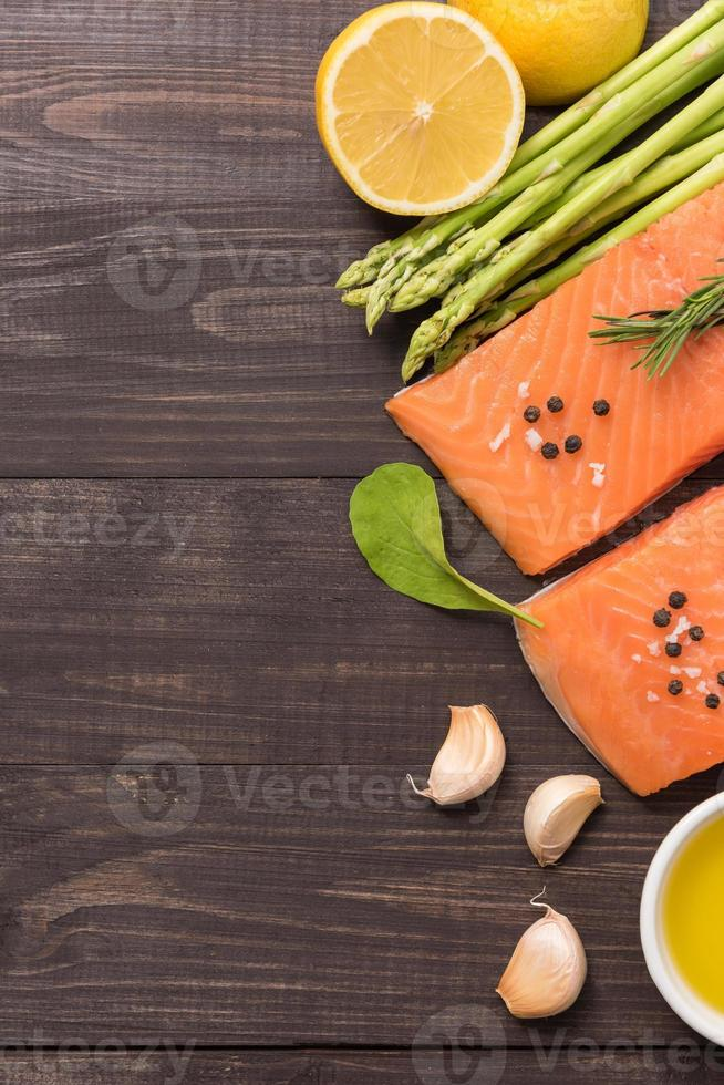 Fresh salmon fillet with spice on wooden background photo