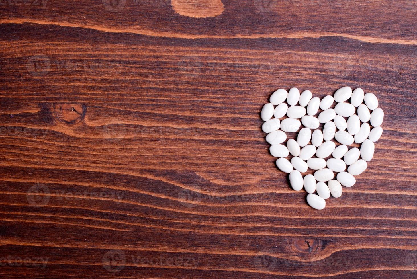 frijoles blancos crudos en el tablero de alimentos dietéticos foto