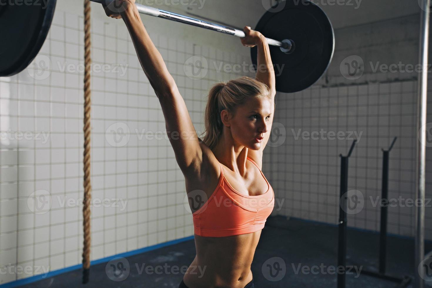 Woman doing gym barbell lifting photo