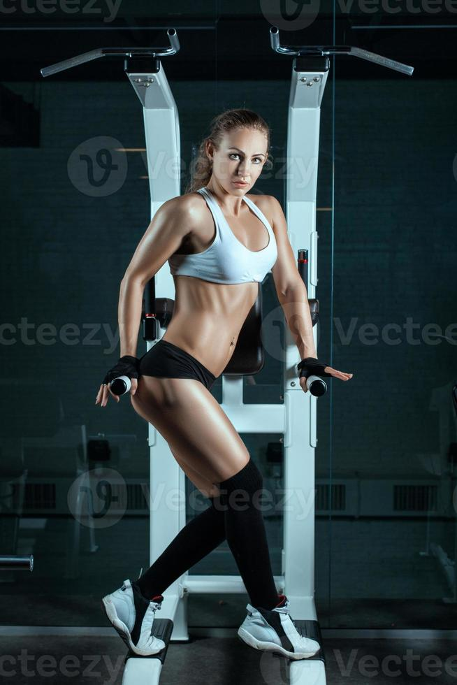 Girl shows her beautiful muscles near the machine for bodybuilders. photo