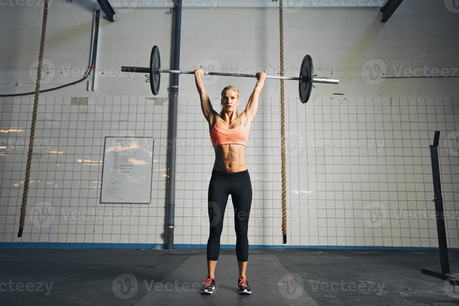 Young strong woman doing weight lifting photo