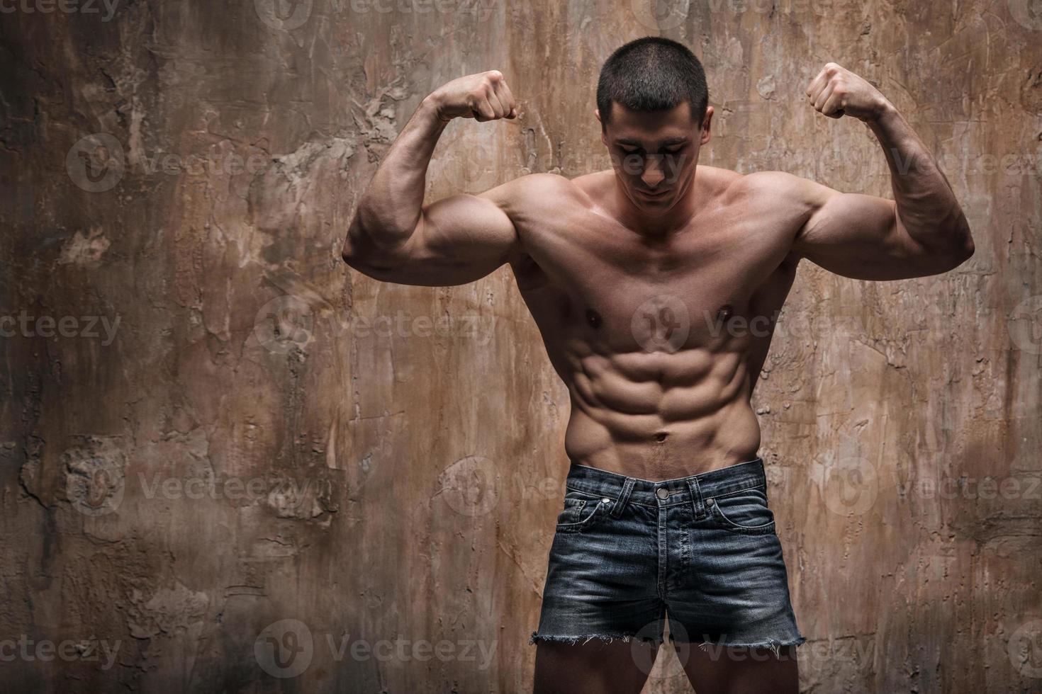 Hombre musculoso sobre fondo de pared. hombre fuerte foto