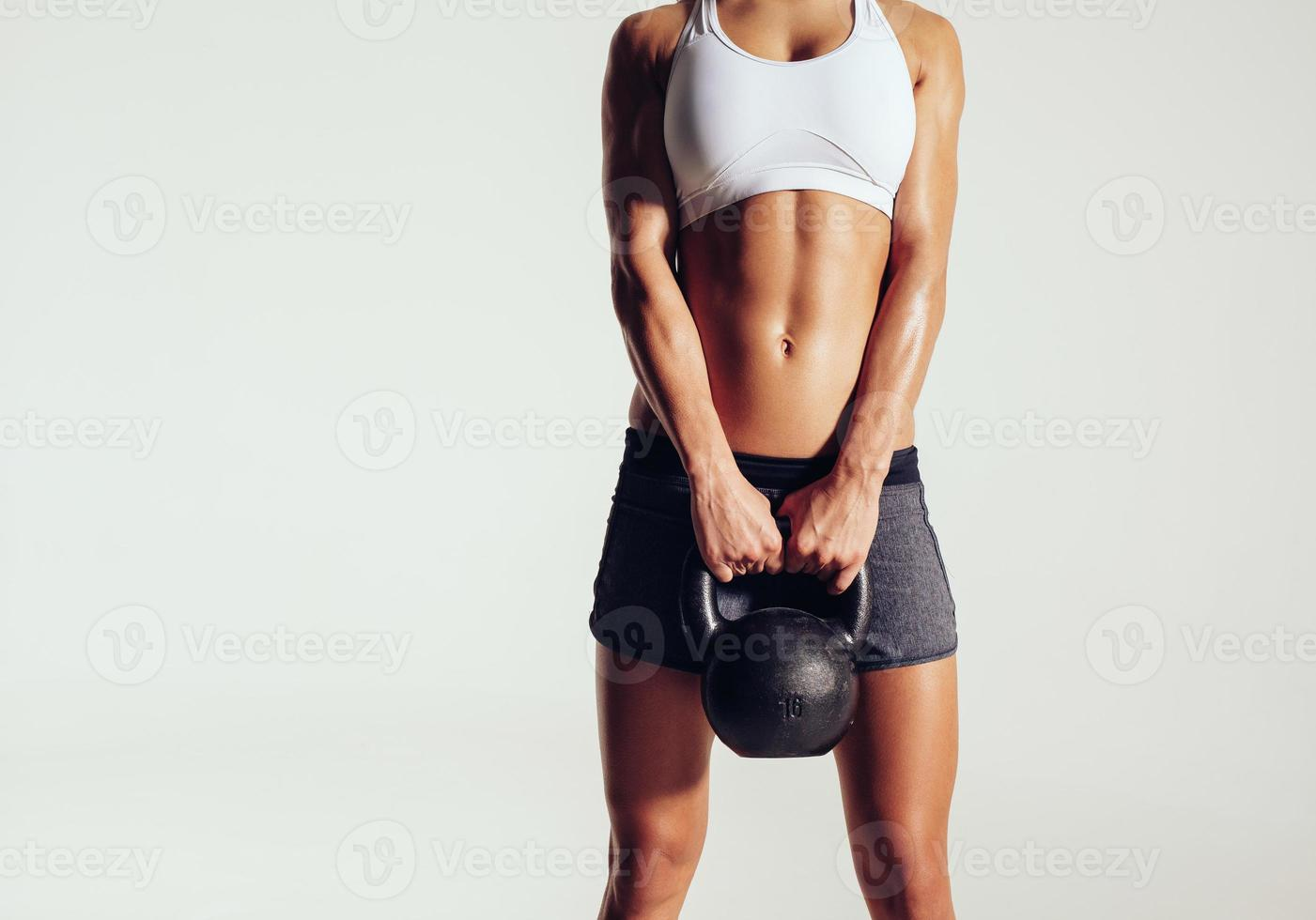 Young woman in sportswear holding a kettle bell photo