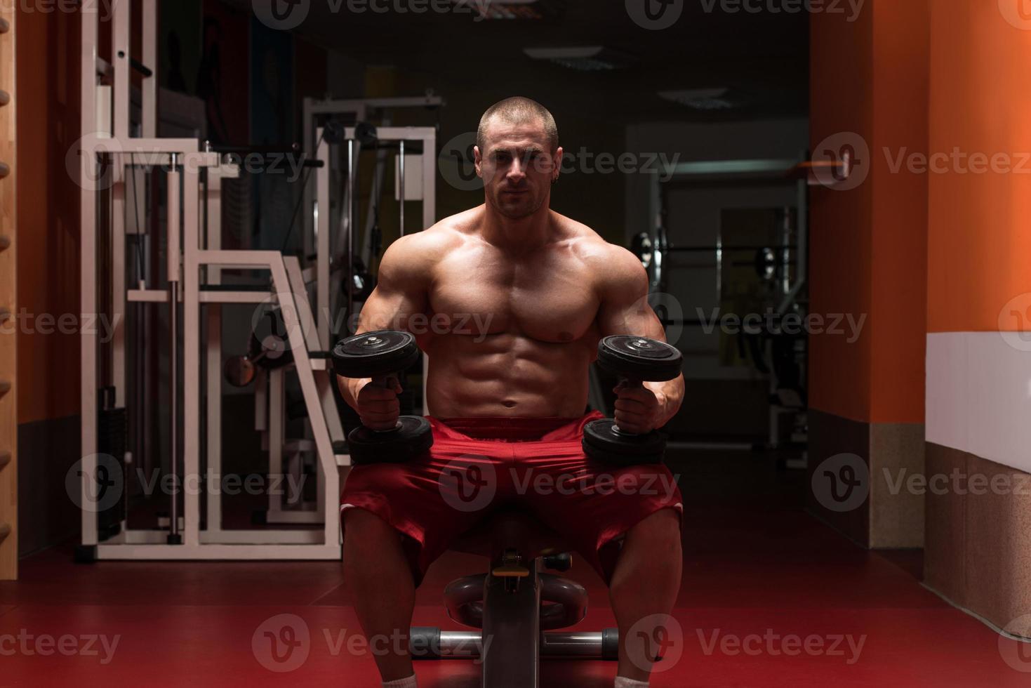 culturista ejercicio de bíceps con pesas foto