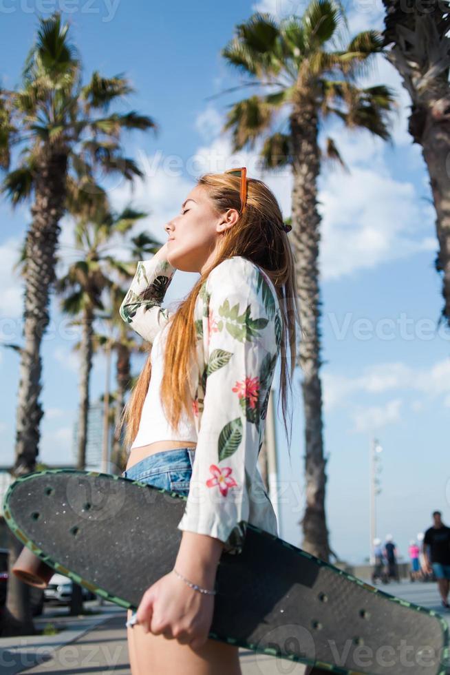 Joven mujer elegante relajante después de montar en su longboard al aire libre foto