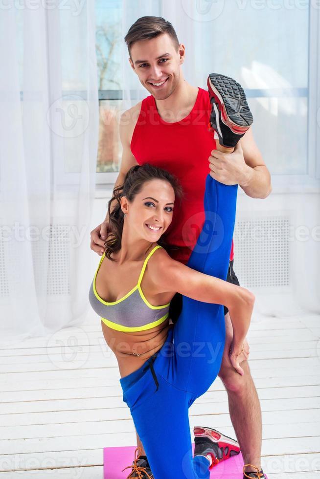 Mujer joven haciendo ejercicios de estiramiento con hombre sonriendo mirando foto