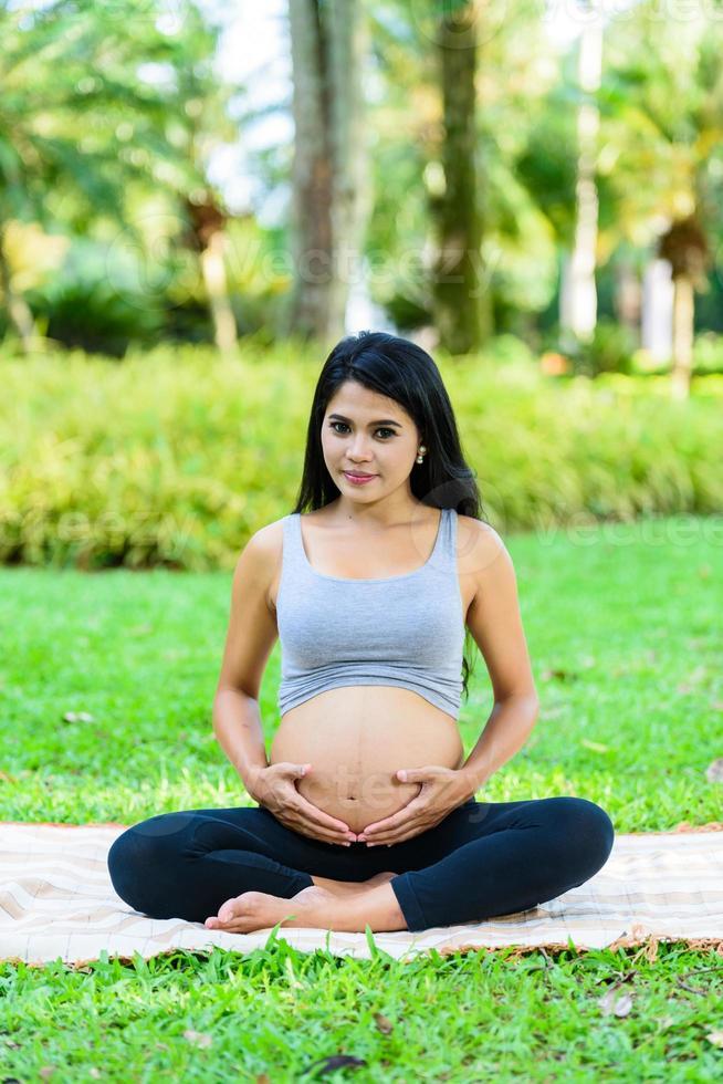 hermosa mujer embarazada yoga en el parque foto