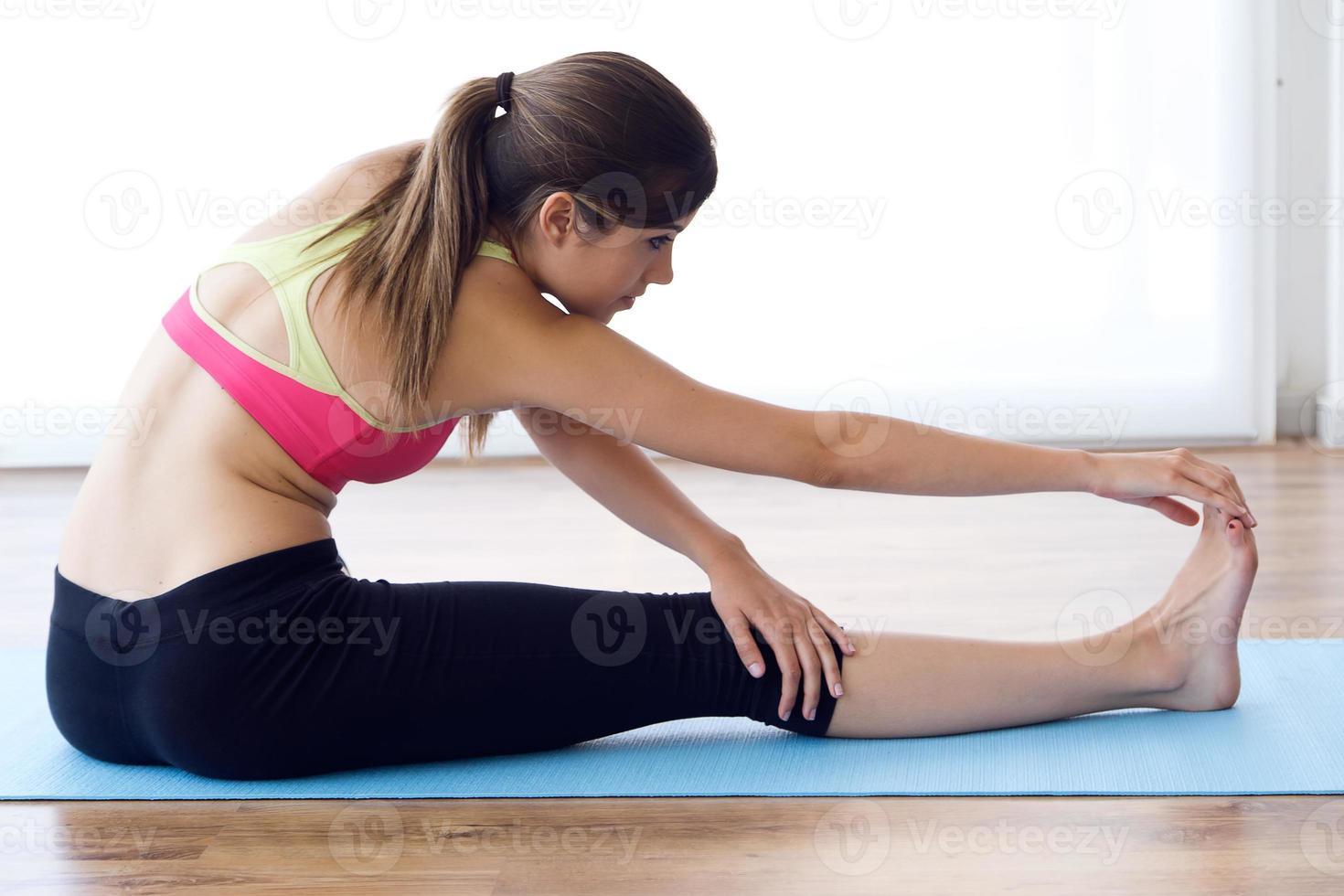 hermosa mujer joven sana haciendo ejercicio en casa. foto
