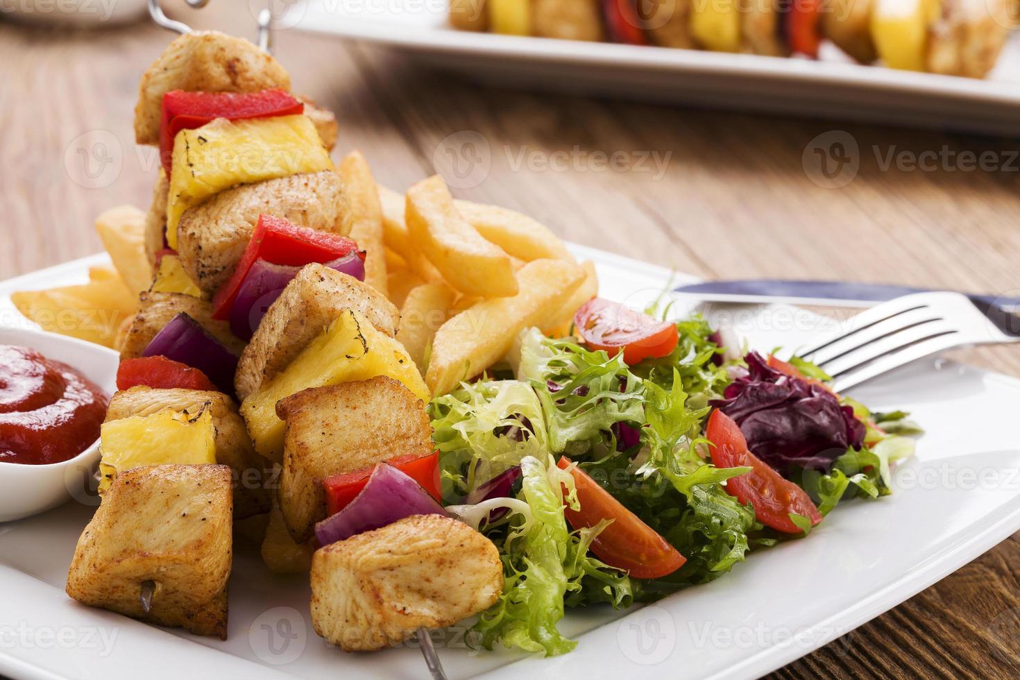 brochetas de pollo a la parrilla con piña, pimiento y cebolla foto