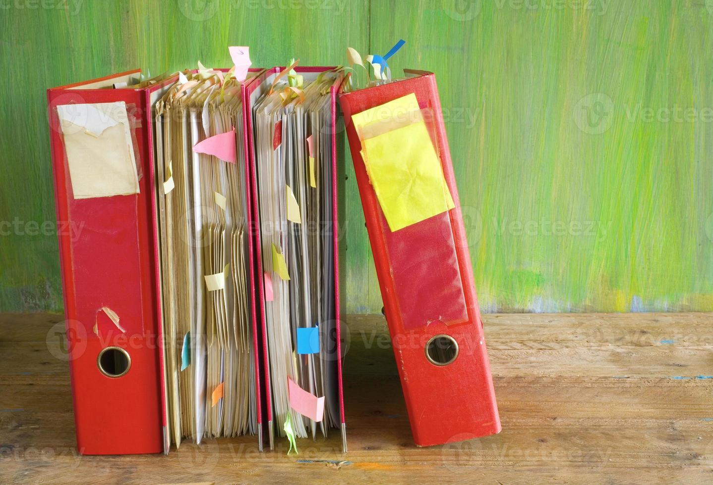 fila de carpetas de archivos con documentos desordenados foto