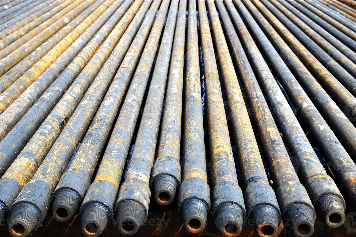 una hilera de tubos de perforación de acero largos y sucios foto