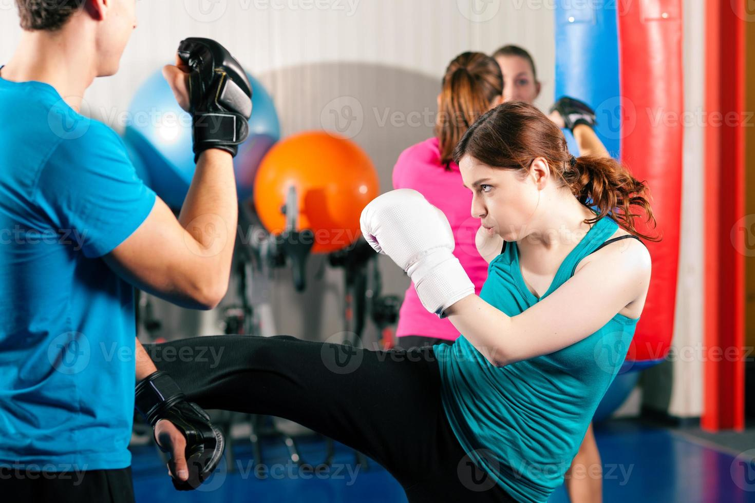 Female kick boxer with trainer in sparring photo
