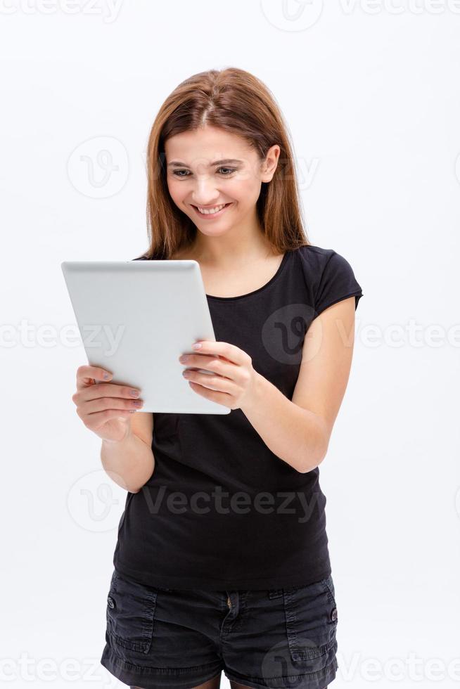heureuse belle mignonne jeune femme à l'aide de la tablette tactile photo