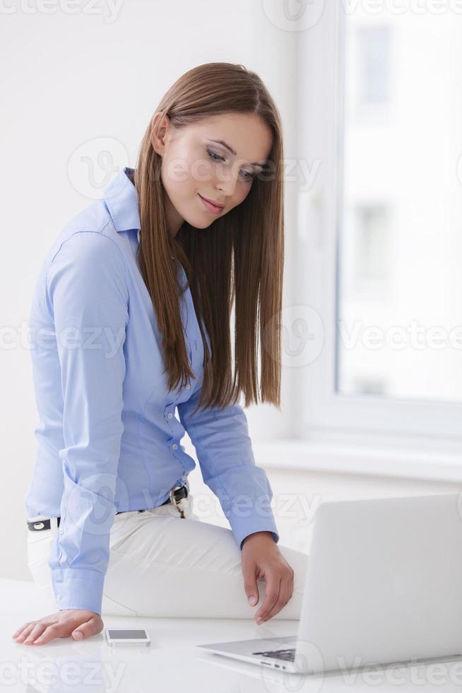 Beautiful businesswoman sitting on desk and looking at laptop photo