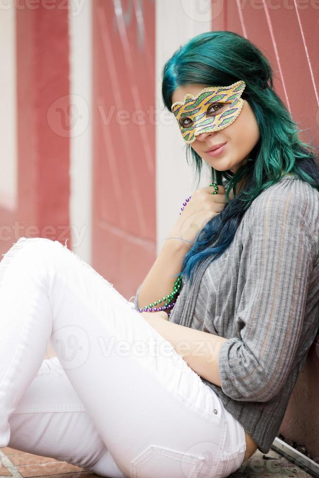 Portrait of young beautiful woman with a mask outdoors photo