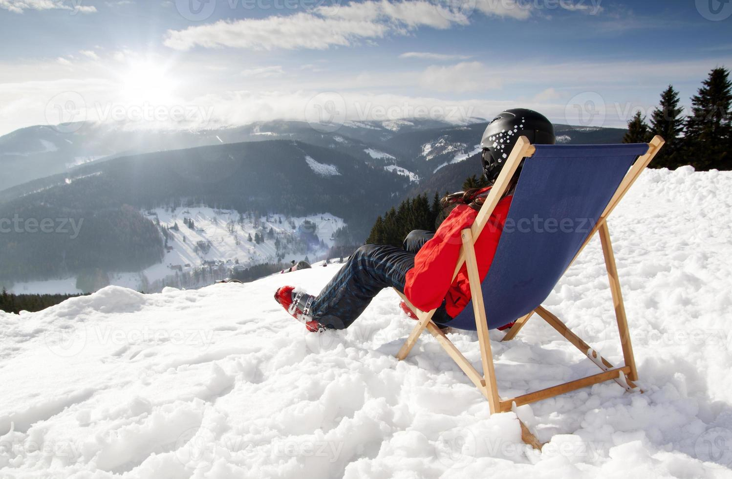 Women at mountains in winter lies on sun-lounger photo