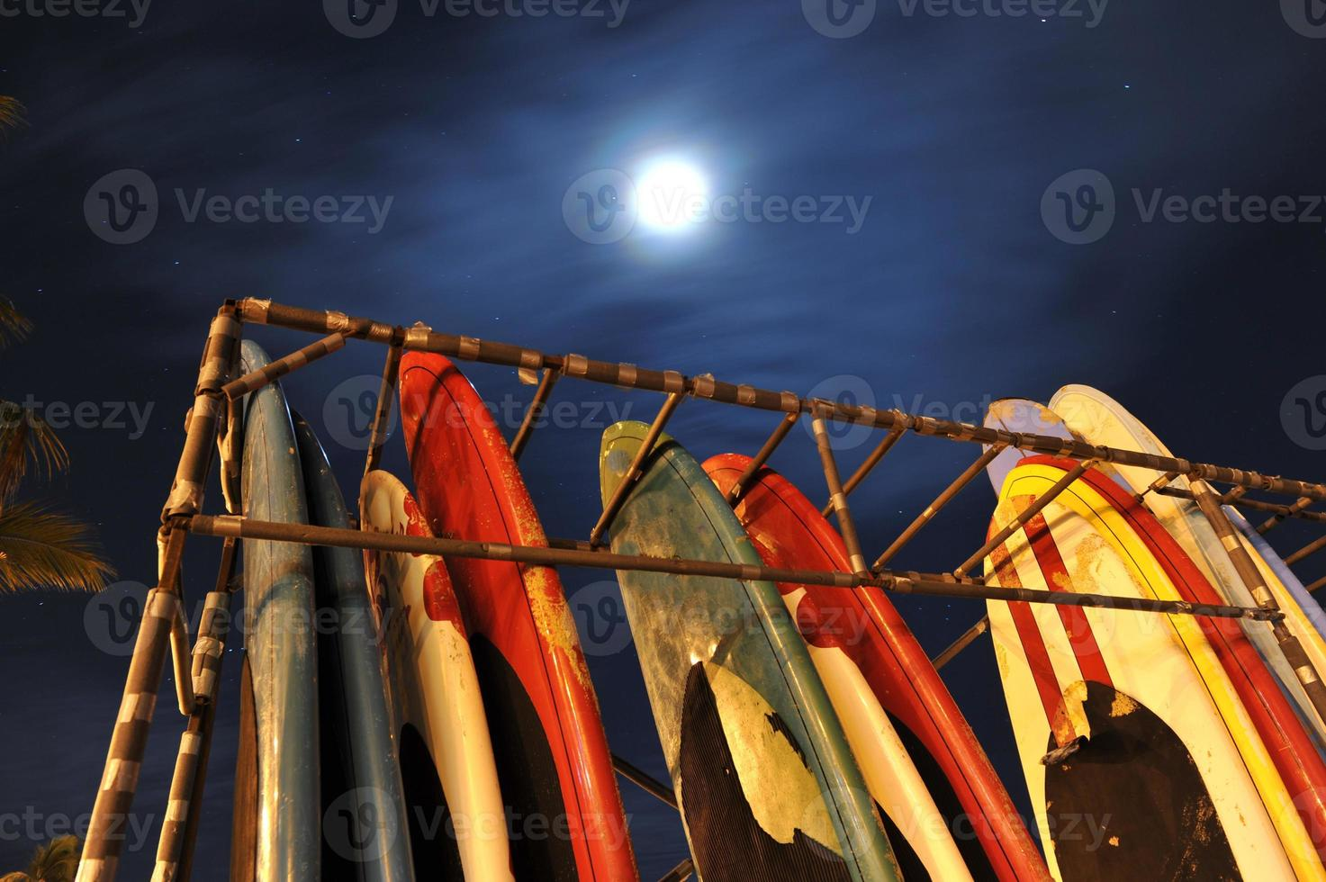 Rack of surfboards with moon in sky photo