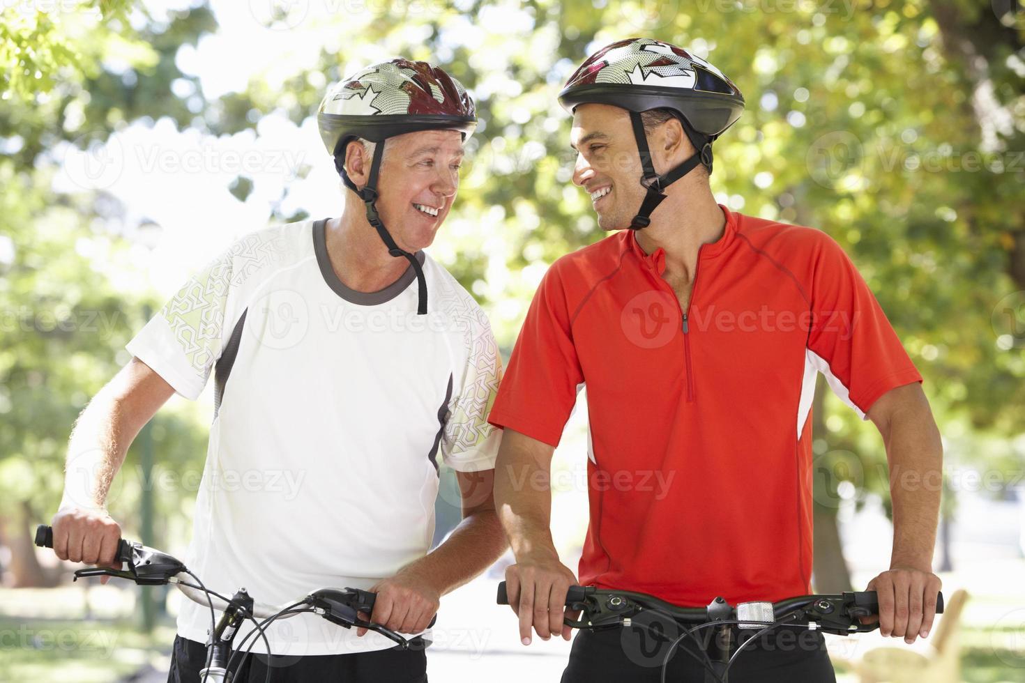 Two Men Cycling Through Park photo