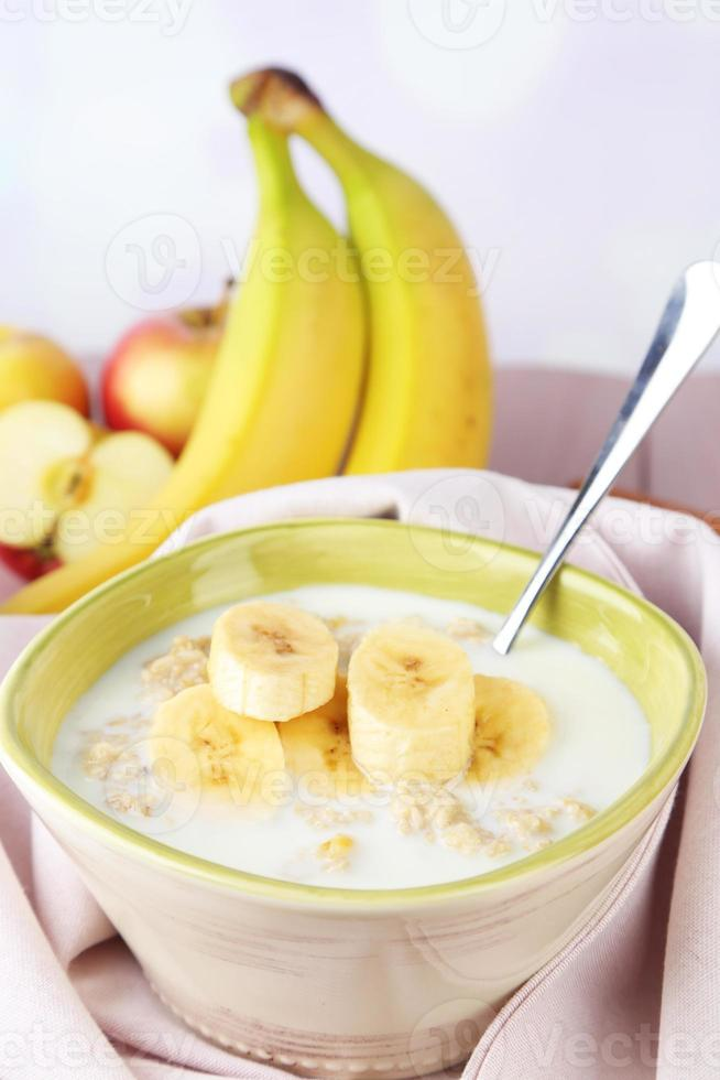Tasty oatmeal with bananas and milk on table photo