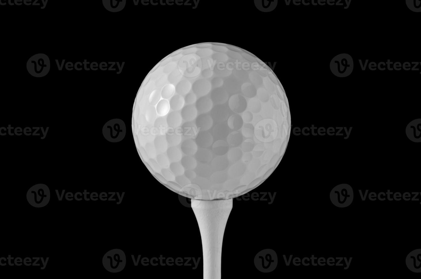 pelota de golf en tee, fondo negro foto