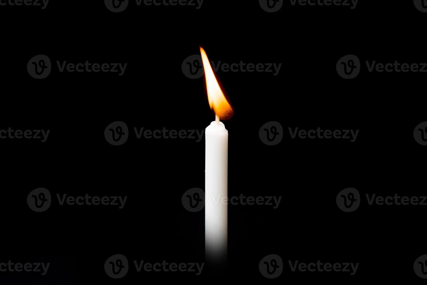 Burning white candle on black background photo