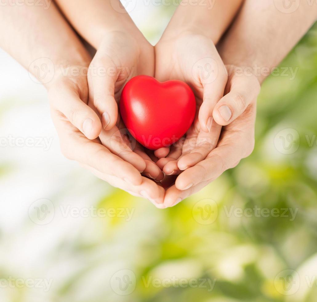 par de manos sosteniendo un corazón juntos foto