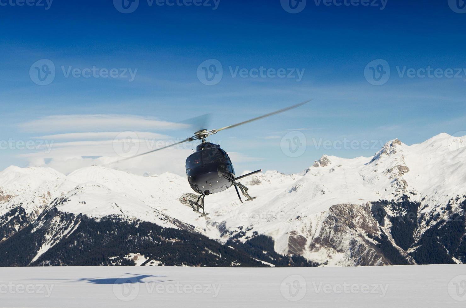 Un helicóptero de rescate de montaña en vuelo por montañas nevadas foto