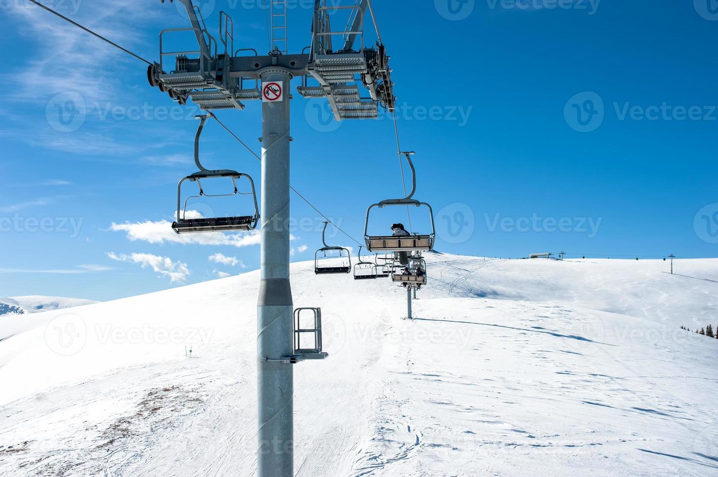 Chairlift on ski slope in mountain resort photo