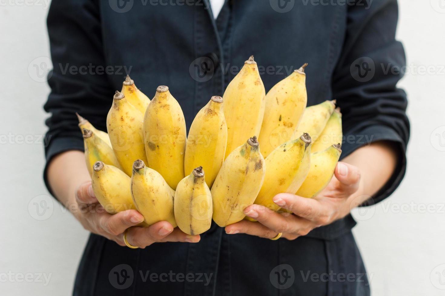 Closeup on young woman holding cluster of bananas photo