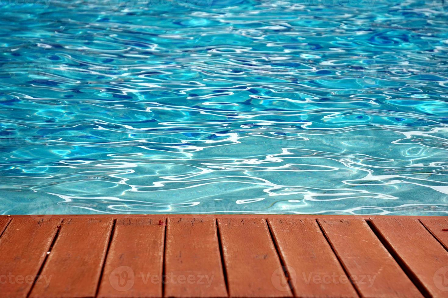 blue swimming pool with wood flooring stripes summer vacation photo
