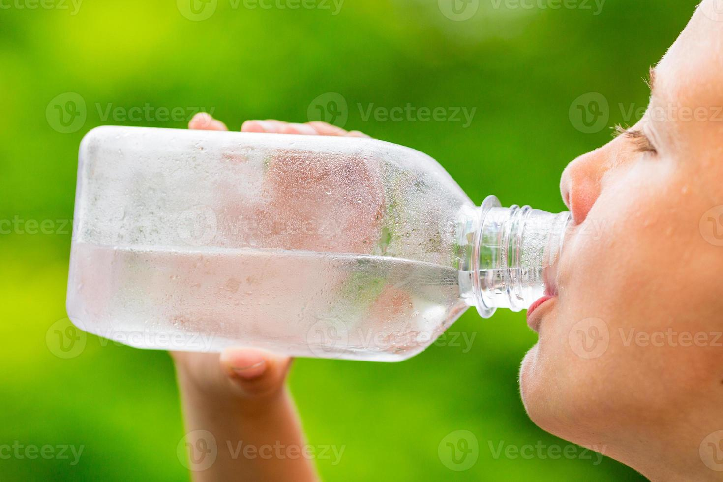 Child drinking clean tap water from transparent plastic bottle photo