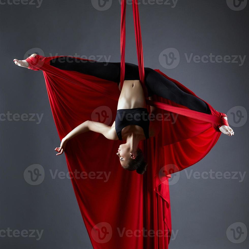 elegante bailarina en sedas aéreas posando boca abajo foto
