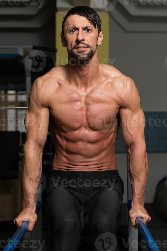 atleta en forma haciendo ejercicio en barras paralelas foto